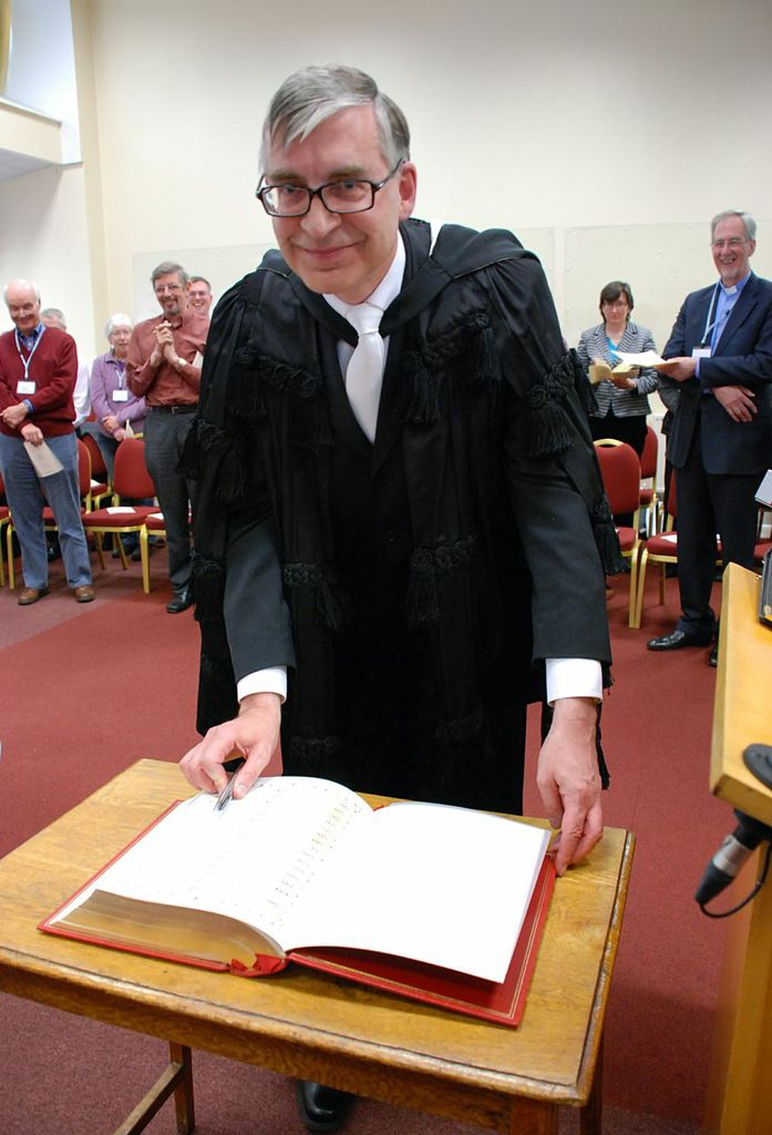 John Ellis signing the Bible. Induction service 16 May 13