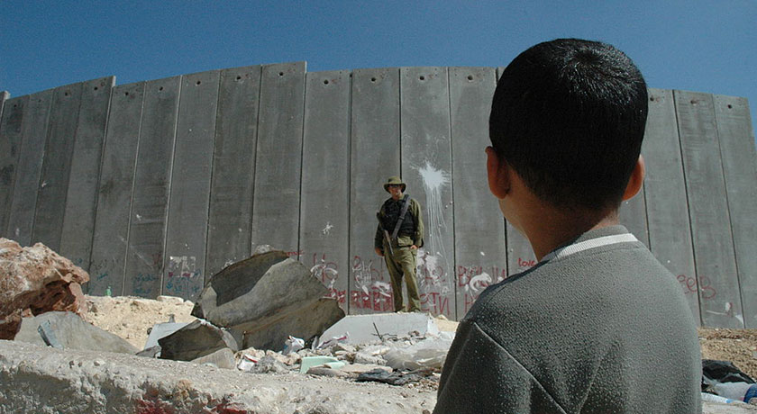 Boy and soldier in front of Israeli wall credit Justin McIntosh news banner