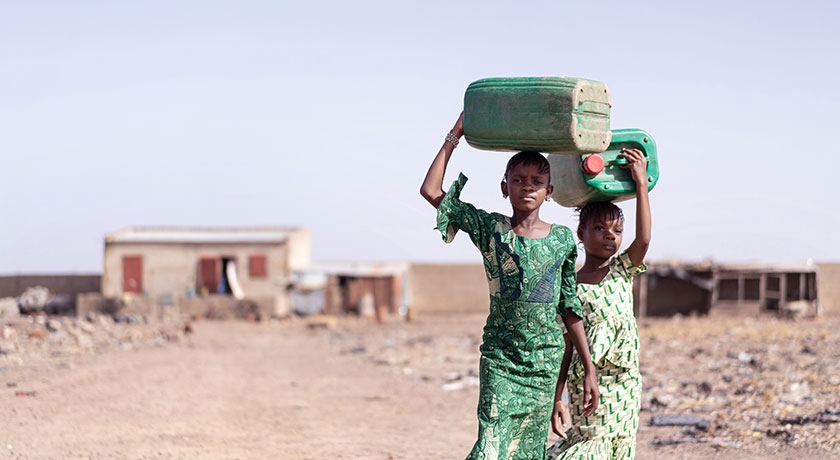 Two girls carrying water containers on their head Riccardo Niels Mayer Adobe Stock