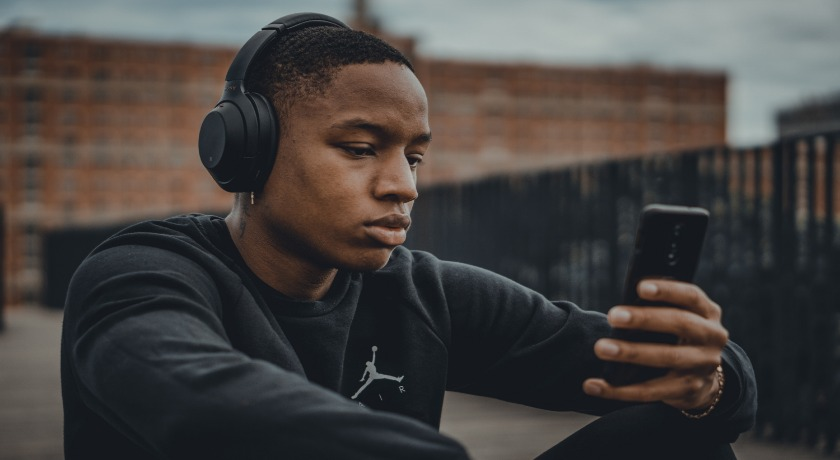 A young man listening to worship on his mobile phone