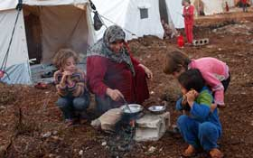 An internally-displaced Syrian cooks in front of her tent in a refugee camp in Atimeh, on the Syrian-Turkish border. © Asmaa Waguih/Reuters